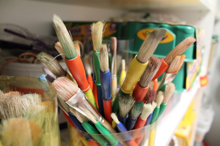 High angle view of various paintbrushes in container on rack