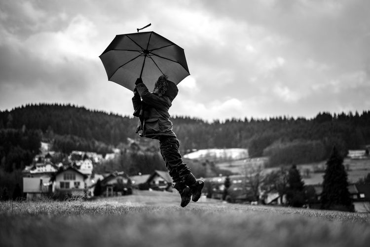 Mary Poppins? Black & White Black And White Blackandwhite Boy Child Childhood Cloud - Sky Day Full Length Grass Hills Holding Landscape Motion Nature One Person Outdoors People Rainy Real People Sky Tree Umbrella Village Young Welcome To Black Break The Mold TCPM Investing In Quality Of Life Perspectives On Nature My Best Photo