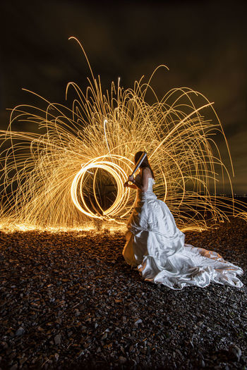 Rear view of woman standing by illuminated wire wool at night
