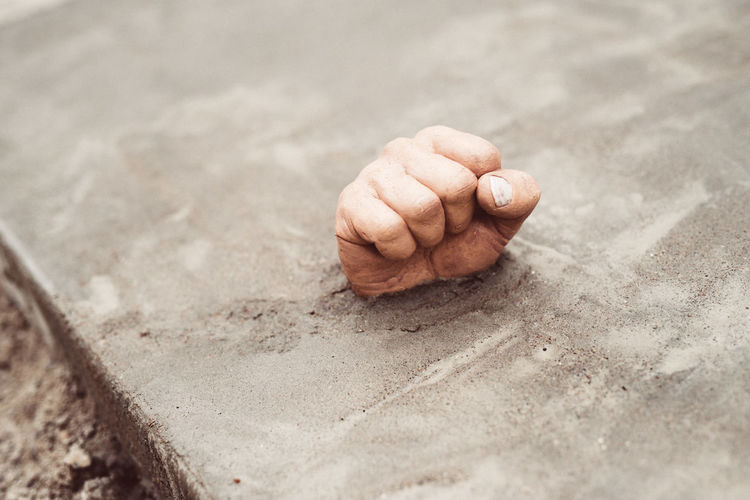 High Angle View Of Clenched Fist Coming Out From Concrete