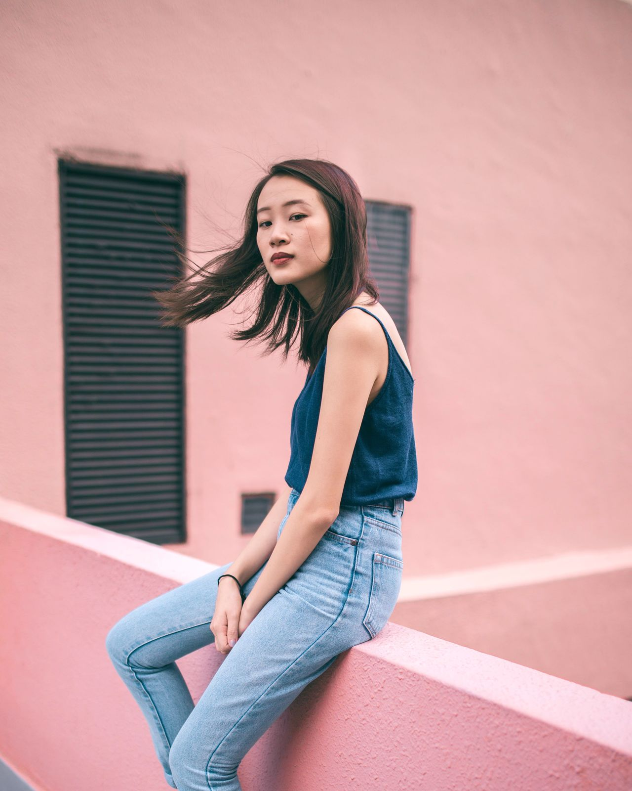 Beautiful young woman against wall