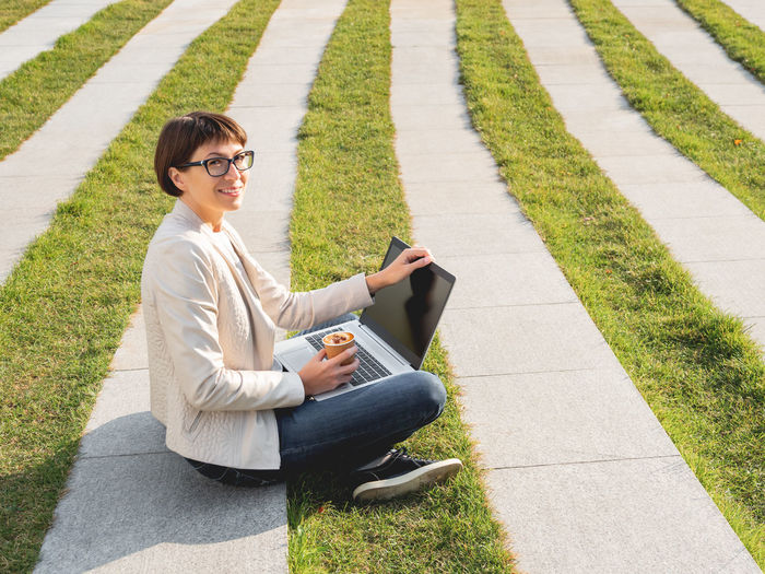 Young woman using phone while sitting on grass