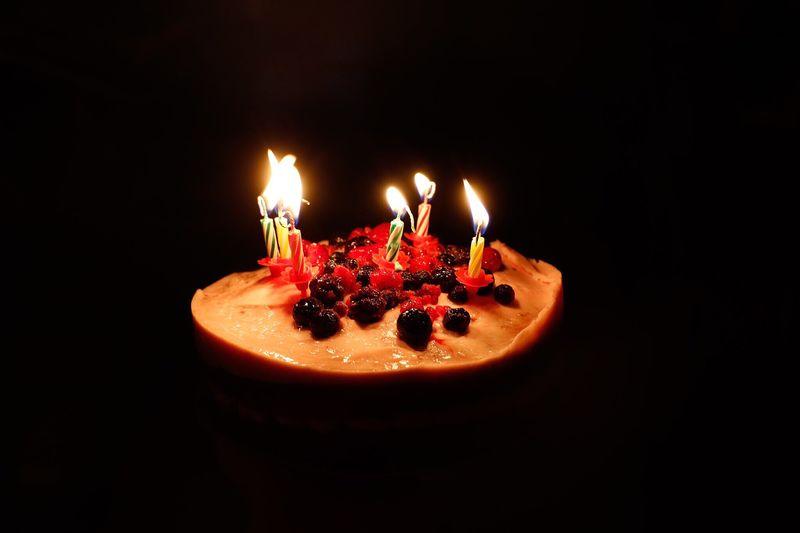 Lit Candles On Birthday Cake In Darkroom