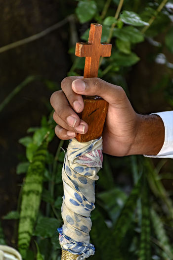 Cropped hand holding cross against plants