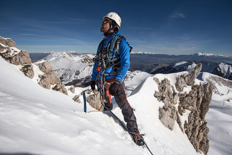 Man On Snowcapped Mountain Against Sky
