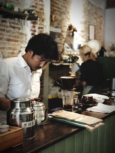 Focus Coffee Cup Coffee - Drink Coffee One Person Business Indoors  Men Real People Table Drink Food And Drink Young Adult Cafe Restaurant Refreshment Bar - Drink Establishment Adult Young Men Container Glass Waist Up Facial Hair Bartender