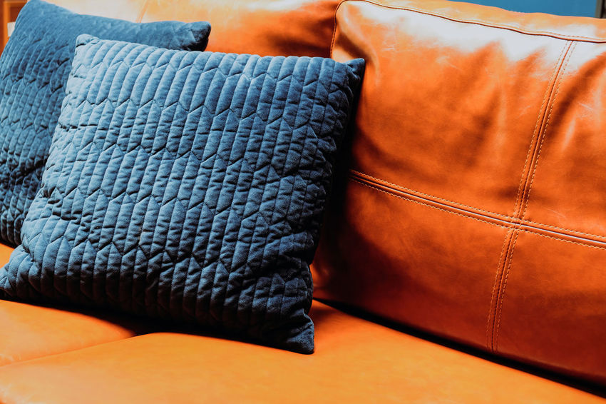 Close up detail of blue pillow on leather sofa Decor Leather Living Orange Pillow Bag Blue Brown Casual Clothing Close-up Clothing Cushion Decoration Decorations Decorative Denim Fashion Furniture Furniture Details Home Interior Indoors  Interior Design Jeans Leather Leather Sofa Living Room No People Orange Color Pattern Pillow Relaxation Sofa Still Life Textile