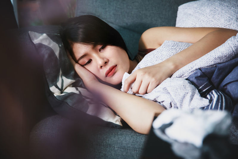 Portrait of a girl sleeping on bed at home