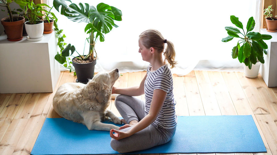 Young woman with cat sitting on floor at home