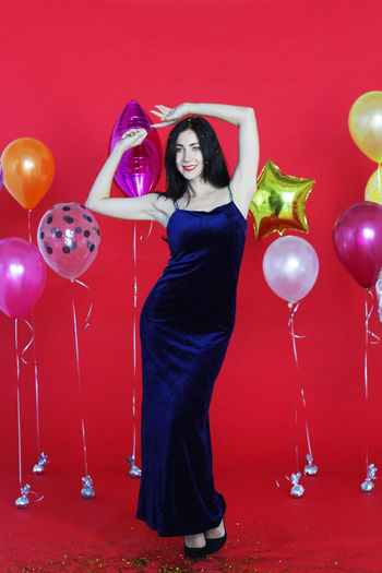 Portrait of a young woman with red balloons