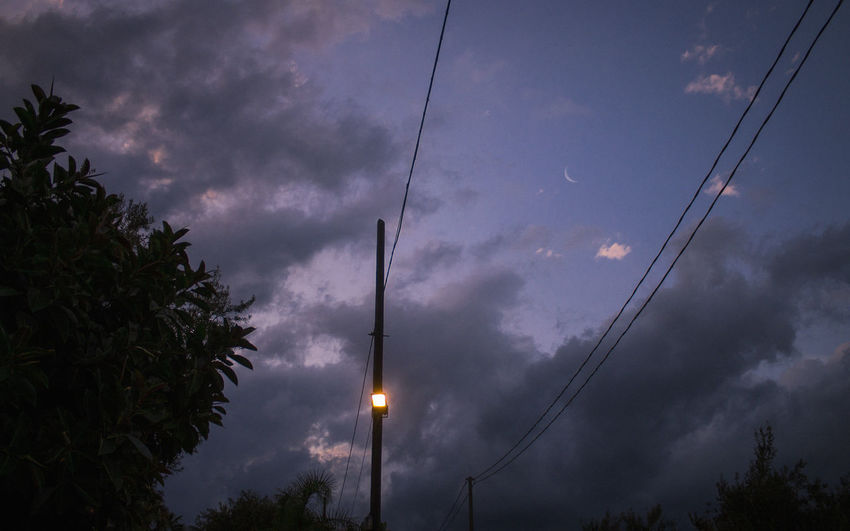 Sky Cloud - Sky Tree Low Angle View No People Plant Nature Dusk Cable Silhouette Electricity  Beauty In Nature Technology Connection Outdoors Illuminated Street Light Street Night Telephone Line Power Supply