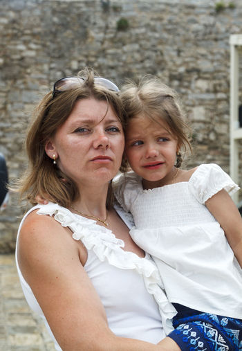 Portrait of mother carrying crying daughter against wall