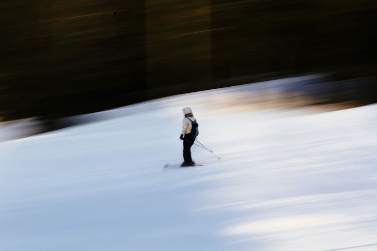 Blurred motion of person skiing on snowcapped mountain