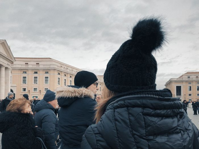 Rear view of people in snow against sky during winter