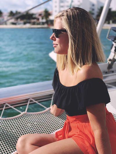 Beautiful woman sitting on boat in sea