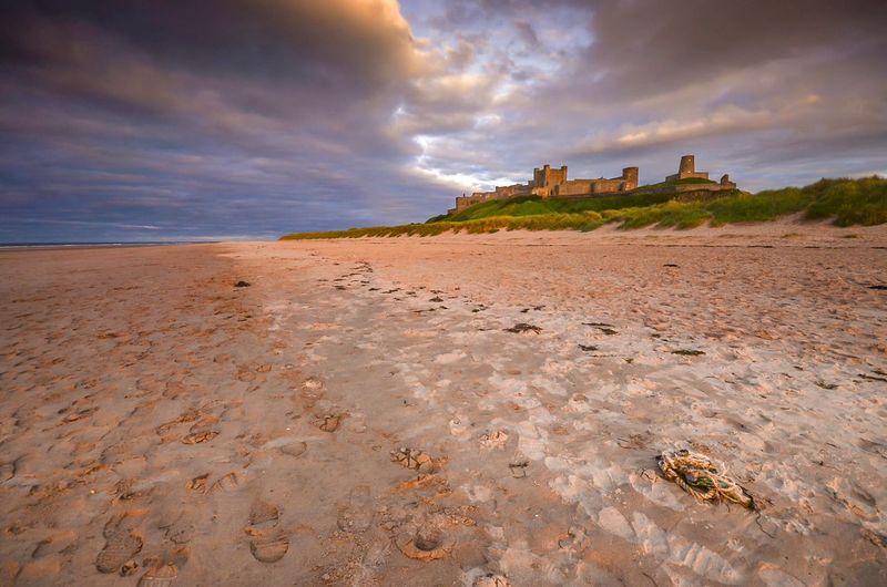 Bamburgh castle by beach against cloudy sky