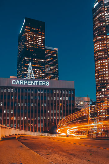 CARPENTERS Illuminated Architecture Built Structure Building Exterior City Night Motion Light Trail Long Exposure Transportation Sky Blurred Motion Building Speed Office Building Exterior Street Road No People Nature Modern Skyscraper Outdoors Financial District