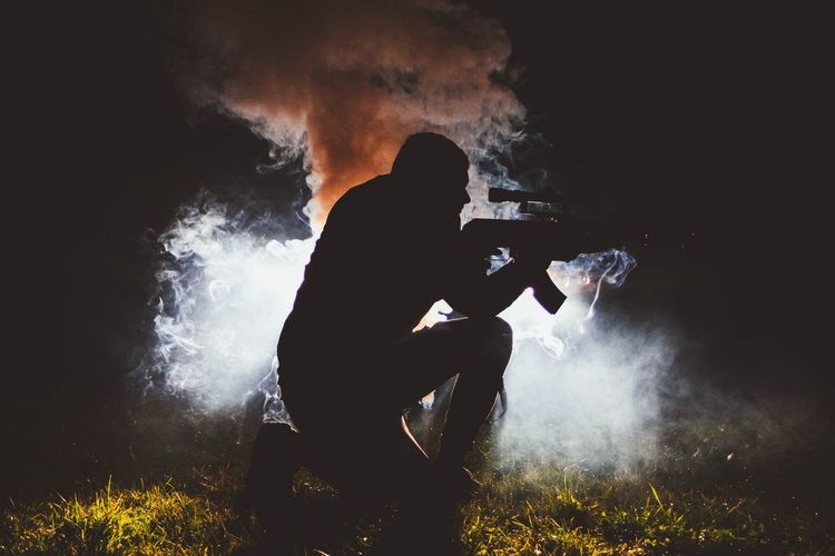 Silhouette man with weapon kneeling on field at night