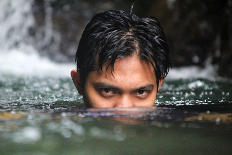 Close-up portrait of man swimming in water