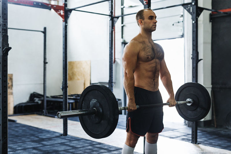 Shirtless man doing deadlift in gym