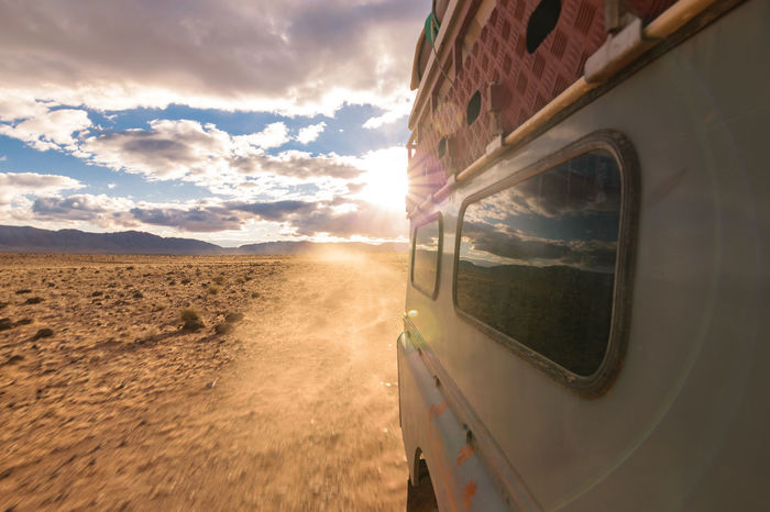 View from the side window of a four by four oldtimer while driving off-road on a dusty road in a stone desert in Morocco. 4x4 Adventure Blue Car Cross Desert Dirty Dust Expedition Explore Flare Off-Road Off-road Vehicle Offroad Oldtimer Road Side Sky Sun Window