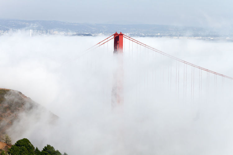 Golden gate bridge amidst clouds during foggy weather