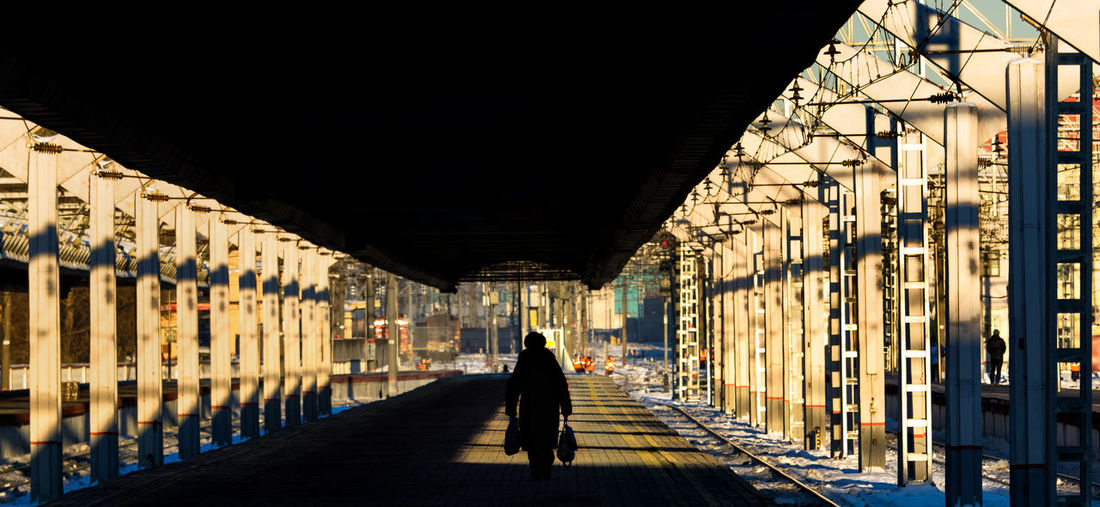 Silhouette woman with bags walking on railroad station platform