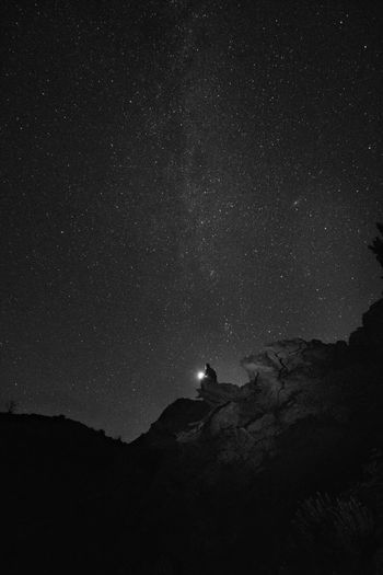Silhouette man sitting on mountain against sky at night
