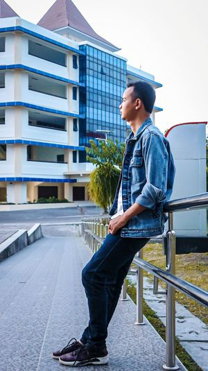 Young man looking away while sitting on railing in city