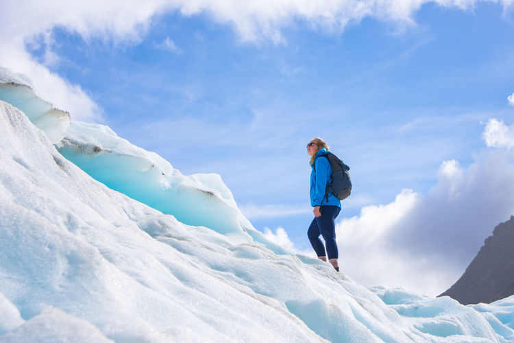 Low angle view of woman standing on snowcapped mountain