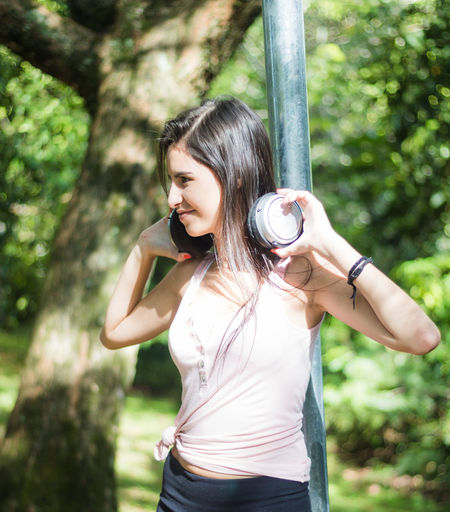 Young Woman With Headphones Standing Against Tree
