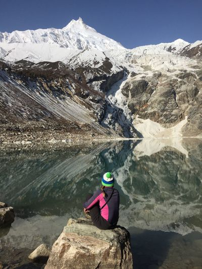 Rear View Of Woman Sitting On Rock By Lake With Snowcapped Mountains Reflection