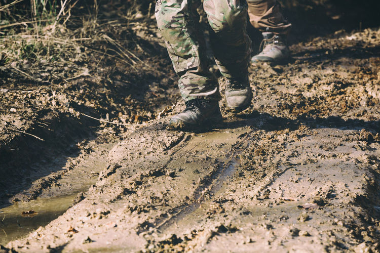 Low section of army soldiers standing on mud