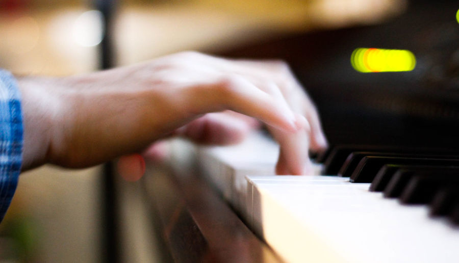 Cropped image of human hand playing piano