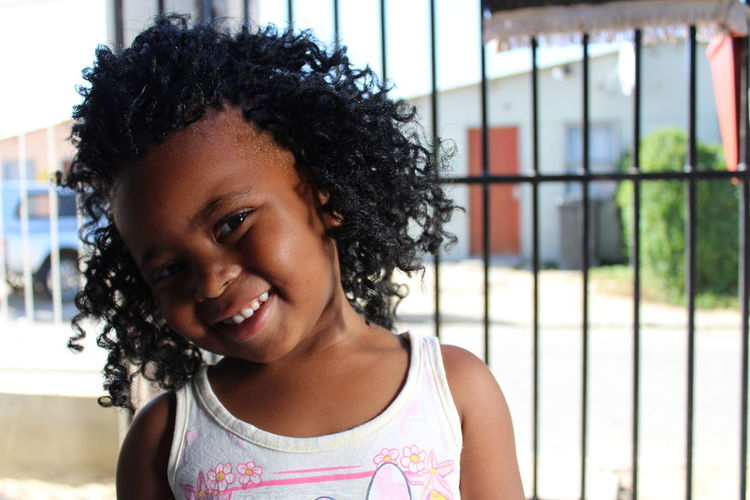 Portrait Of Cute Smiling Girl With Curly Hair Standing By Fence