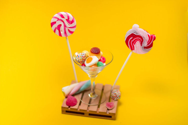 Candy Colored Background Dairy Product Dessert Food Food And Drink Freshness Frozen Frozen Food Ice Cream Ice Cream Sundae Indoors  Indulgence Lollipop Pink Color Studio Shot Sweet Sweet Food Temptation Unhealthy Eating Yellow