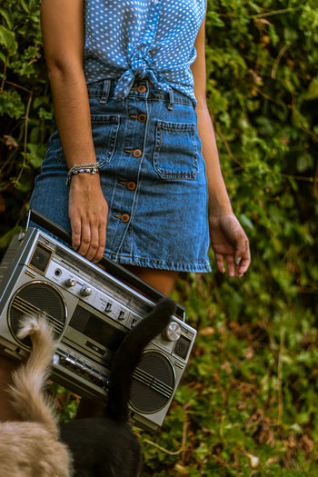Low section of woman holding retro radio standing outdoors with cats and tails