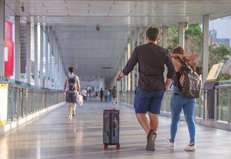 Rear view of people walking on walkway in city