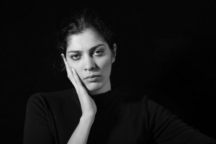 Portrait of sad woman over black background