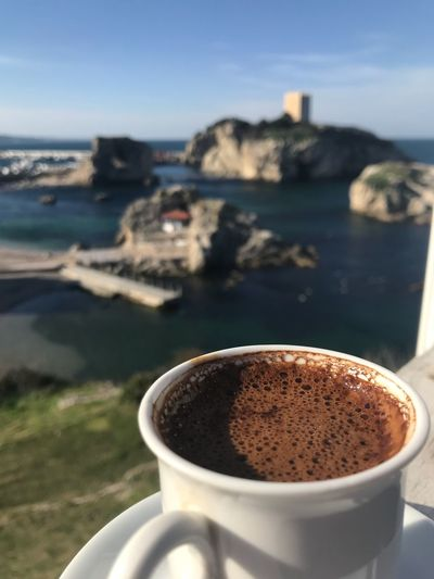 Close-up of coffee on table against sea