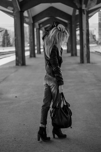 Full length of woman holding purse standing on road