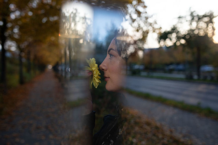 Double exposure image of woman with flower against road