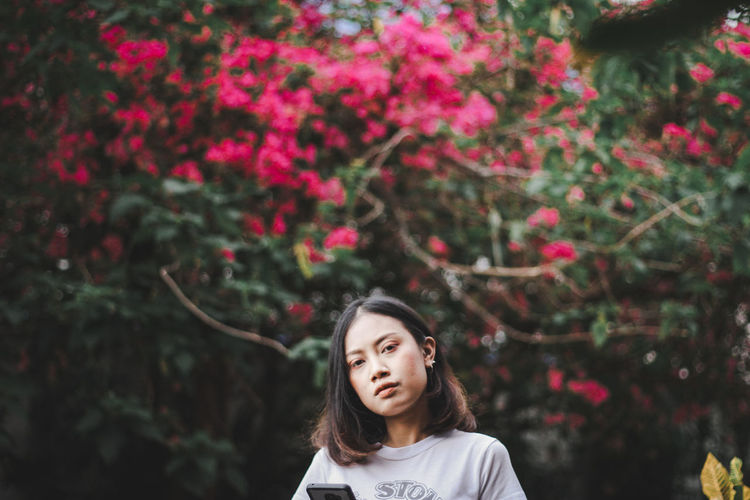 Portrait of young woman against tree