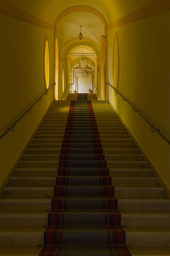 Architecture The Way Forward Direction Staircase Steps And Staircases Indoors  Built Structure Railing Illuminated Arch Building Lighting Equipment Diminishing Perspective Low Angle View No People Wall - Building Feature Absence Empty Yellow Pattern Ceiling Aisle