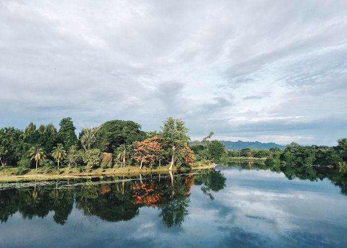 Scenic view of river with clouds reflection amidst trees