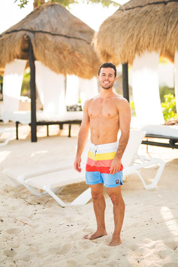 Handsome Man Front View Full Length Happiness Leisure Activity Lifestyles Looking At Camera Muscular Build Muscular Build Yet Feminin Nature One Person Outdoors Portrait Sand Sea Shirtless Smiling Standing Summer Surfing Swimming Trunks Thatched Roof Vacations Young Adult Young Man