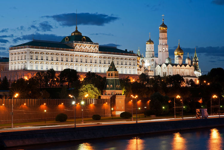 Moscow kremlin by river against sky in city at dusk