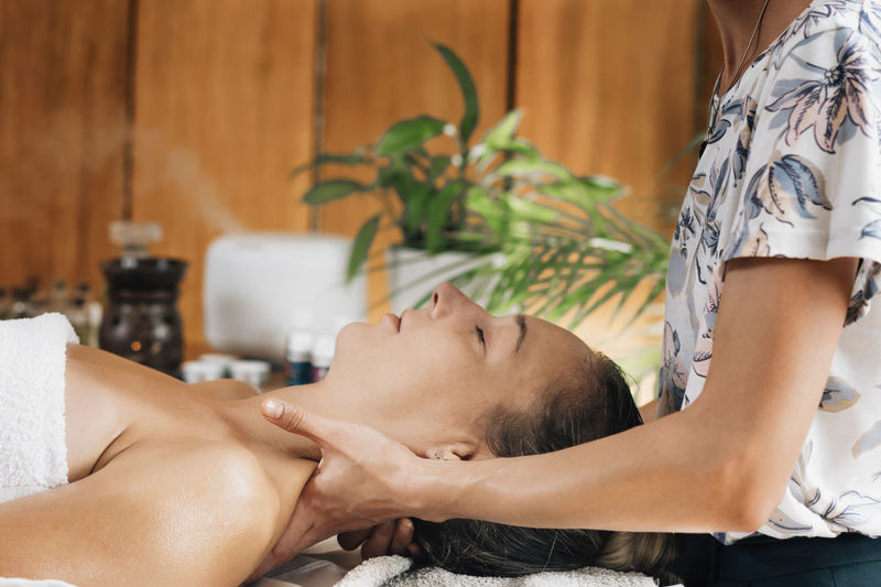 Aromatherapy massage, masseuse massaging client with therapeutic ethereal oil
