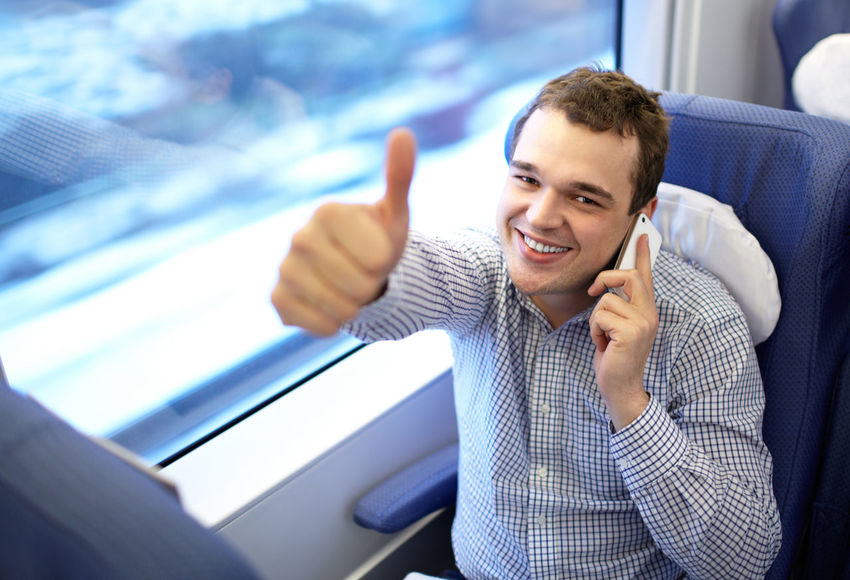 25-30 Active Businessman Caucasian Communication Commuter Customer  Finger Handsome High Speed Journey Man Passenger Sign Smart Phone Smile Talking Thumbs Up Train Young