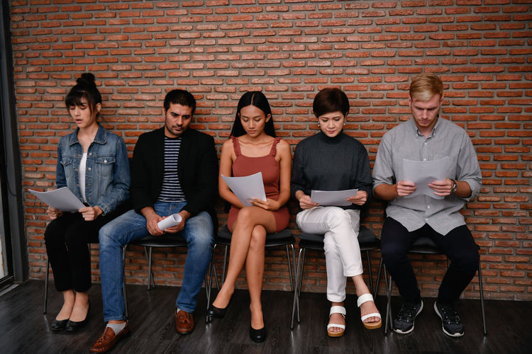 Candidates with resume sitting on chairs against brick wall in office